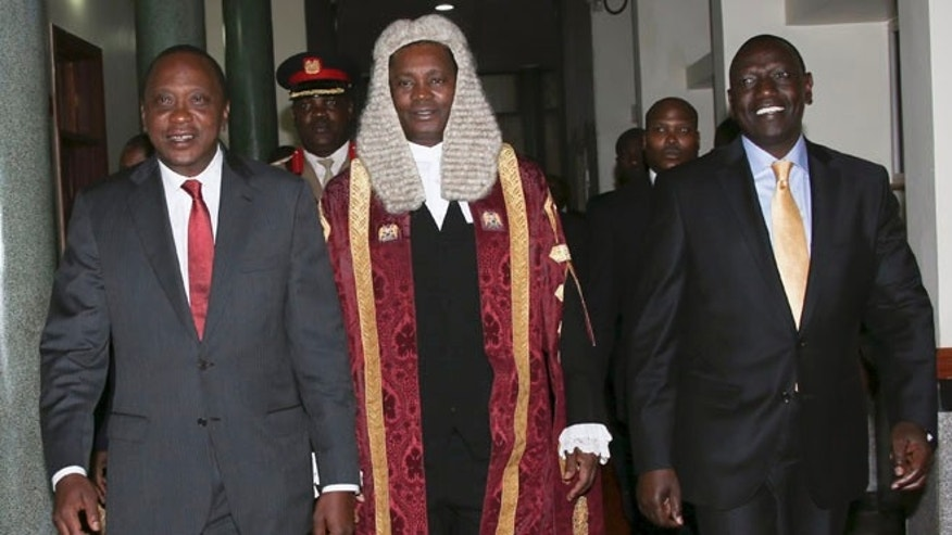 Oct. 6, 2014: President Uhuru Kenyatta, left, walks with Deputy President William Ruto, right, and Speaker of the National Assembly Justin Muturi, center, on his arrival at the parliament in Nairobi, Kenya (