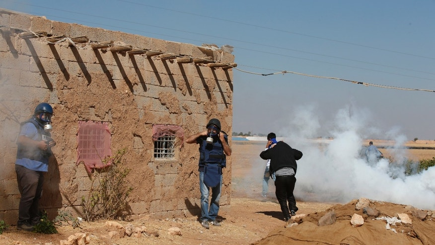 Oct. 6, 2014 - Turkish Kurds and members of the media run to avoid the effects of tear gas fired by Turkish forces to disperse the Kurds on the outskirts of Suruc, at the Turkey-Syria border, as fighting intensified between Syrian Kurds and ISIS militants.