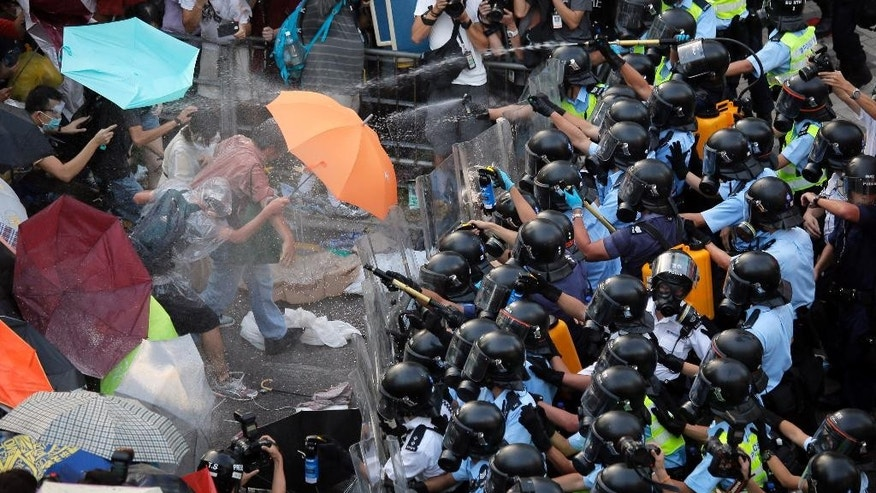 FILE - In this Sept. 28, 2014 file photo, riot police use pepper spray against protesters after thousands of people block a main road to the financial central district outside the government headquarters in Hong Kong. The legacy of the 1989 crackdown in Tiananmen Square looms larger in Hong Kong than in mainland China, where the Communist Party has virtually erased all public mention of it. In this former British colony, hundreds of thousands attend candlelight vigils each anniversary to commemorate the grim end to the Beijing movement that was vanquished before many of the pro-democracy protesters in Hong Kong's streets were even born. (AP Photo/Vincent Yu, File)