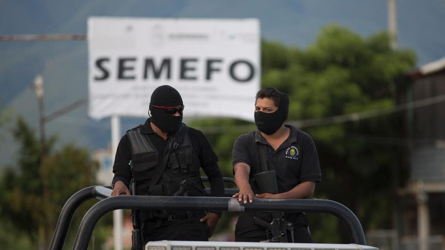 Masked police officers stand guard atop a vehicle oudside of the morgue in Iguala Mexico, Sunday Oct. 5, 2014. Relatives are demanding answers after security forces investigating the role of municipal police in clashes a week ago found a mass grave, raising fears the pits might hold the bodies of 43 students missing since last week in the violence that also resulted in six shooting deaths. (AP Photo/Eduardo Verdugo)