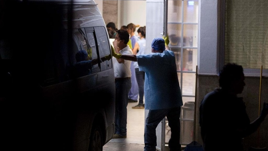 A forensic workers stand inside of the morgue in Iguala Mexico, Sunday Oct. 5, 2014. Mexican forensic experts recovered 28 charred bodies from a clandestine grave on the outskirts of this city where police engaged in a deadly clash with student protesters a week ago, Guerrero state's chief prosecutor said Sunday. Authorities said the corpses were too badly damaged for immediate identification and he could not say whether any of the dead could be some of the 43 college students reported missing after the confrontation with police. (AP Photo/Eduardo Verdugo)