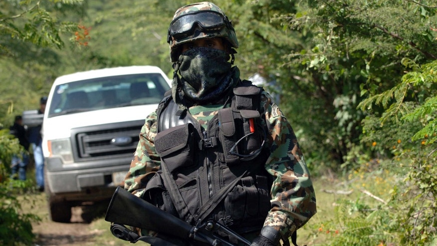 Oct. 4, 2014 - A Mexican navy marine guards the road leading to the site where an alleged clandestine mass grave was found near the city of Iguala, Mexico. Mexican officials said the grave holding 28 bodies was found outside a town where violence last weekend resulted in 6 deaths and the disappearance of 43 students.