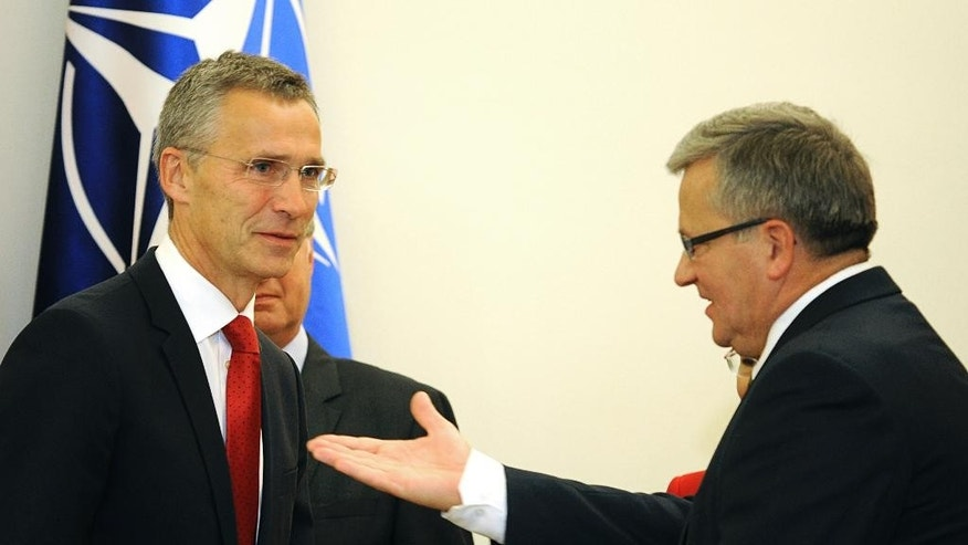 Polish President Bronislaw Komorowski, right, gestures  before talks with NATO Secretary General Jens Stoltenberg, left, in Warsaw, Poland, Monday, Oct. 6, 2014.  Stoltenberg came to Poland for his first visit abroad after taking over the leadership of the alliance. (AP Photo/Alik Keplicz)