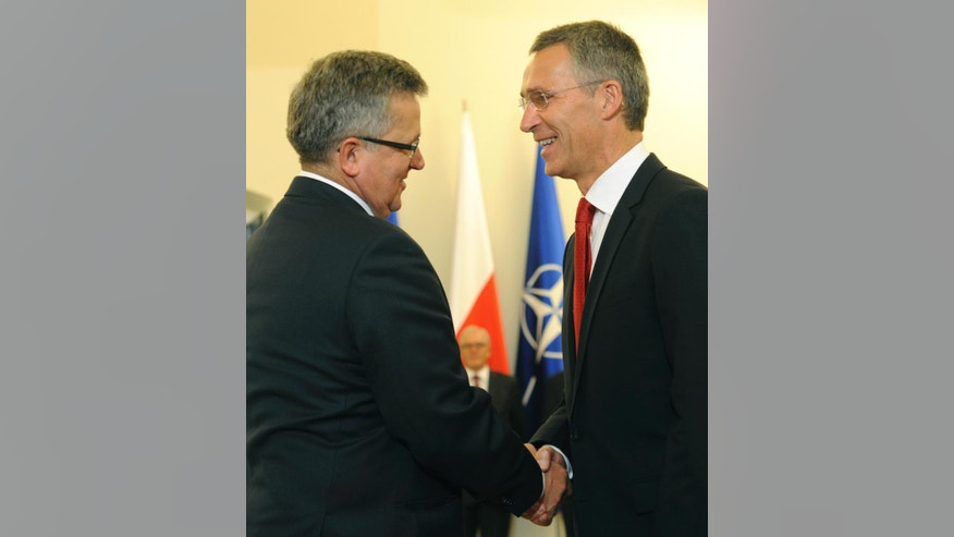 Polish President Bronislaw Komorowski shakes hands with NATO Secretary General Jens Stoltenberg, right, before talks in Warsaw, Poland, Monday, Oct. 6, 2014. Stoltenberg came to Poland for his first visit abroad after taking over the leadership of the alliance. (AP Photo/Alik Keplicz)