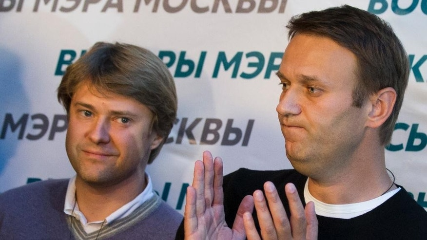 "In this photo taken on Sunday, Sept. 8, 2013, Vladimir Ashurkov, left, a top aide of top Russian opposition leader and anti-corruption blogger Alexei Navalny, right, who has been under house arrest since February 2014, attends a news conference at his headquarters in Moscow, Russia. Vladimir Ashurkov wrote on Twitter Monday that he had requested asylum in the United Kigdom ""due to political persecution"" by authorities. Ashurkov didn't say whether he had yet received a response from British authorities. (AP Photo/Alexander Zemlianichenko)"