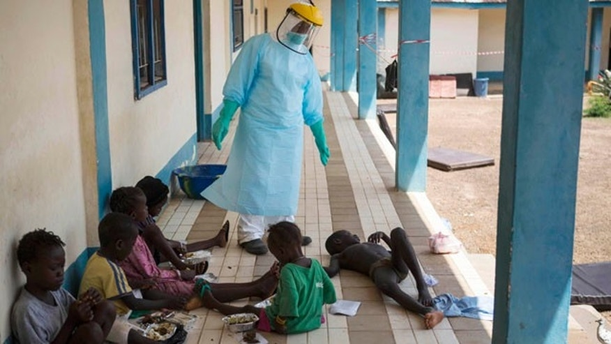 October 4, 2014: A health official dressed in protective gear examines children suffering from the Ebola virus at Makeni Arab Holding Centre in Makeni, Sierra Leone. Makeni is one of three districts recently quarantined by the government.  (AP Photo/Tanya Bindra)