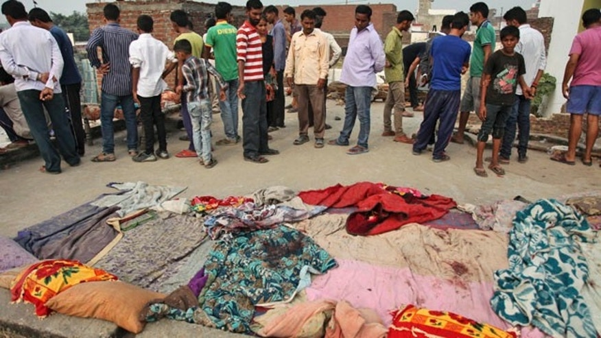 October 6, 2014: Indian villagers gather near bed sheets stained with blood in alleged firing from the Pakistans side while the residents were asleep on roof of their house, at Masha da kothe village, in Arnia Sector near the India-Pakistan international border, about 30 miles from Jammu. (AP Photo/Channi Anand)