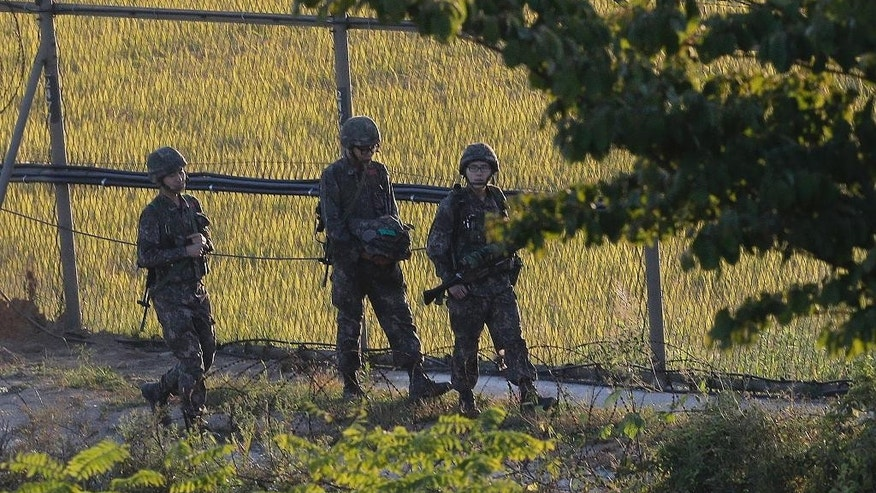 South Korean army soldiers patrol through the wire fences near the demilitarized zone between the two Koreas in Paju, South Korea, Tuesday, Oct. 7, 2014. Warships from the rival Koreas exchanged warning shots Tuesday after a North Korean ship briefly violated the disputed western sea boundary, a South Korean defense official said. (AP Photo/Ahn Young-joon)