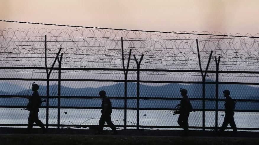 South Korean army soldiers patrol through the wire fences near the demilitarized zone between the two Koreas in Paju, South Korea, Tuesday, Oct. 7, 2014. Warships from the rival Koreas exchanged warning shots Tuesday after a North Korean ship briefly violated the disputed western sea boundary, a South Korean defense official said.(AP Photo/Ahn Young-joon)