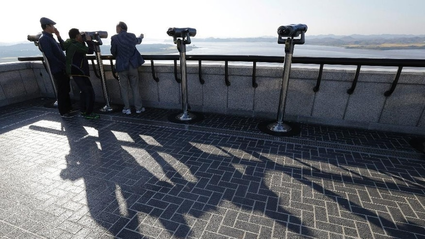 Visitors look at North Korea at the unification observation post near the demilitarized zone between the two Koreas in Paju, South Korea, Tuesday, Oct. 7, 2014. Warships from the rival Koreas exchanged warning shots Tuesday after a North Korean ship briefly violated the disputed western sea boundary, a South Korean defense official said.(AP Photo/Ahn Young-joon)