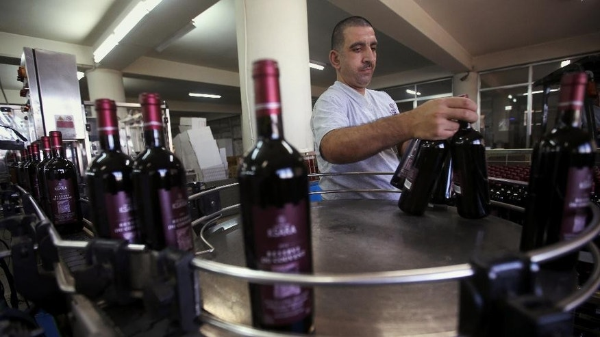 In this Sept. 8, 2014, photo, a Lebanese worker arranges Ksara red wine bottles at Chateau Ksara winery complex in the Bekaa valley, east Lebanon. In Syria and Lebanon, boutique wineries mainly run by Christians have endured despite decades of unrest and the fact that Islam, the majority faith in the region, forbids both the production and consumption of alcohol. (AP Photo/Hussein Malla)