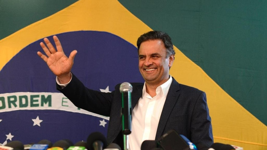 Aecio Neves, presidential candidate of the Brazilian Social Democracy Party, PSDB, waves during a press conference in Belo Horizonte, Brazil, Sunday, Oct. 5, 2014. Official results showed Sunday that President Dilma Rousseff will face challenger Aecio Neves in a second-round vote in Brazil's most unpredictable presidential election since the nation's return to democracy nearly three decades ago.(AP Photo/Eugenio Savio)