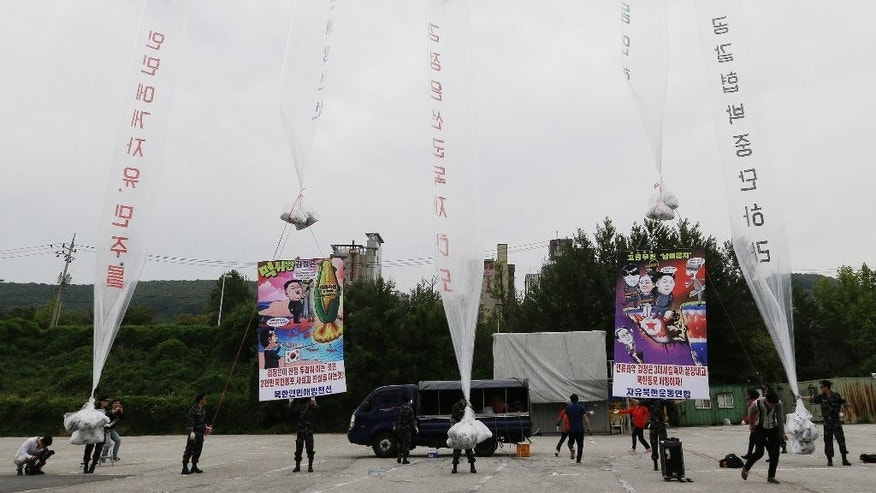 "In this Sept. 21, 2014 photo, North Korean defectors prepare to release balloons to let them fly to the North, carrying leaflets and banners condemning North Korean leader Kim Jong Un and his government's policies during a rally against North Korea in Paju, near the border with North Korea, South Korea. The writing on the balloons and banners reads ""End the world's worst three generation dictatorship and Down with Kim Jong Un."" One recent survey by a Seoul civic group of about 400 defectors suggested that one in every two defector families in the South send home money, mostly between 500,000 won ($470) and 3 million won ($2,820) per year. They do this even though most defectors struggle to make a living in the highly competitive, well-educated South: Their average monthly wage is about 1.4 million won ($1,320), about half the pay of an average South Korean worker. (AP Photo/Ahn Young-joon)"