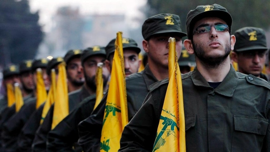 FILE - In this Nov. 12, 2010 file photo, Hezbollah fighters hold their party flags, as they parade during the opening of new cemetery for colleagues who died in fighting against Israel, in a southern suburb of Beirut, Lebanon. An explosion along the Israel-Lebanon border wounded two Israeli soldiers Tuesday, Oct. 7, 2014,  and the military then fired toward Hezbollah positions in southern Lebanon in the most serious incident between the enemy countries in months. Hezbollah issued a statement on the group's Al Manar TV station claiming responsibility for the blast in Shebaa on Tuesday,  saying it targeted an Israeli patrol.   (AP Photo/Hussein Malla, File)