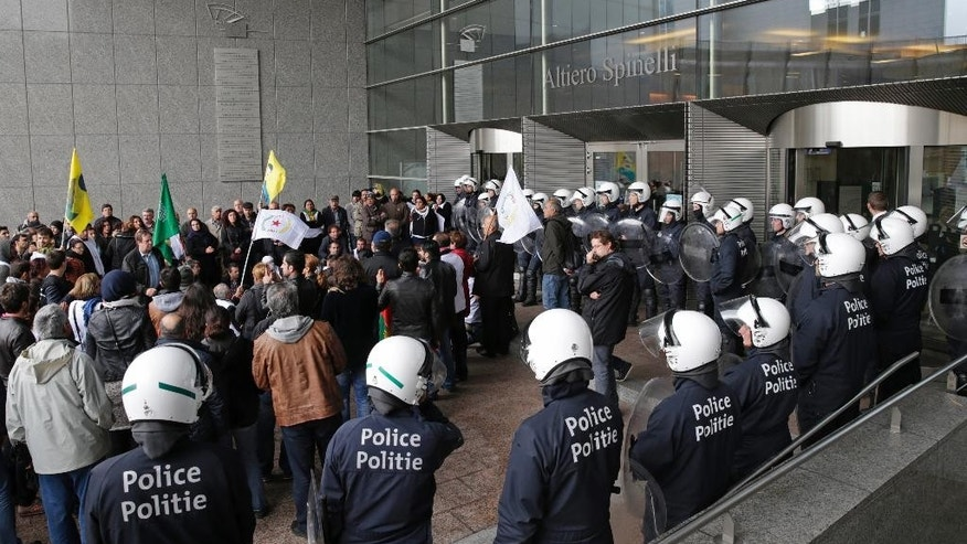 Belgian riot police encircle Kurdish protesters in front of the entrance of the European Parliament in Brussels, on Tuesday, Oct. 7, 2014. Kurdish protesters forced their way past Belgian police into the European parliament to call for help for the town of Kobani on the Syrian-Turkish border. (AP Photo/Yves Logghe)