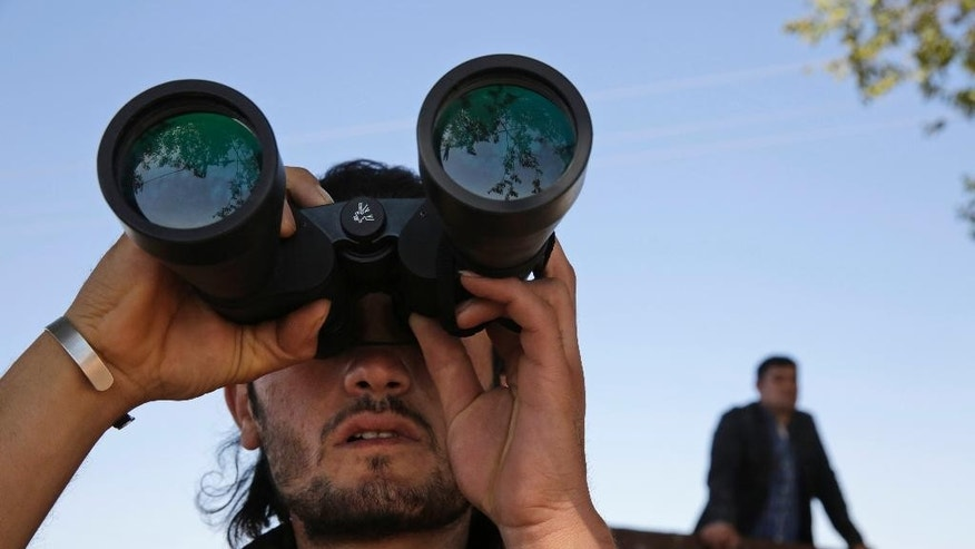 FILE -  In this Monday, Oct. 6, 2014 file photo, a Turkish Kurd, standing on the  the Turkey-Syria border, uses binoculars to watch fighting between militants of the Islamic State group and Kurdish forces in Kobani, Syria, on outskirts of Suruc, Turkey.    The Kurds of Syria and Iraq have become a major focal point in the war against the Islamic State group, with Kurdish populations in both countries coming under significant threat by the militants' lightening advance.  The cooperation between Kurds in these countries underscores their loyalty, not to the nations in which they live, but to the shared dream of one day establishing an independent and unified Kurdistan, or Land of the Kurds. (AP Photo/Lefteris Pitarakis< File)