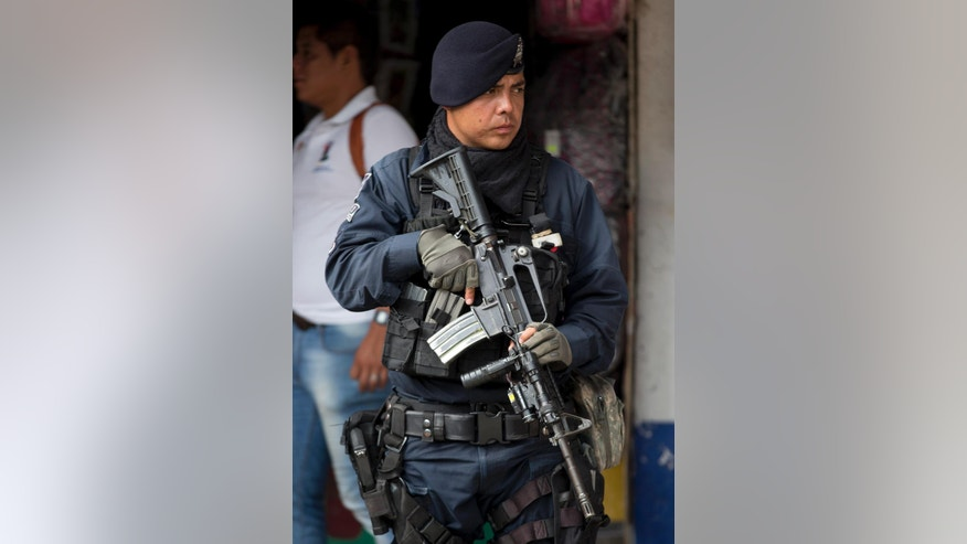 A police officer stands outside the municipality in Iguala, Mexico, Monday, Oct. 6, 2014. Federal officials on Monday disarmed local police and took over security after an attack on students that left at least six dead and 43 missing. Officials say that police officers were in league with a local gang called the Guerreros Unidos in carrying out the attack, and sent a new preventative unit of the federal police to keep order and help look for the missing. (AP Photo/Eduardo Verdugo)