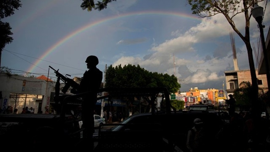 October 6, 2014: A soldier stands under a rainbow outside the municipality in Iguala, Mexico. Federal officials on Monday disarmed local police and took over security after an attack on students that left at least six dead and 43 missing. (AP Photo/Eduardo Verdugo)
