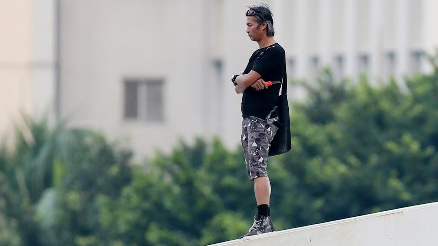 In this Oct. 5, 2014 photo, a man who is identified by local media as Leung Siu Hung, a stuntman, holding a cutter, threatens to jump off the bridge to protest the Occupy Central movement outside the government headquarters in Hong Kong's Admiralty. In the Hong Kong protests, not all is as it seems. In the chaos of mass street protests, murky characters come into play. The Hong Kong Stuntman's Association denied on Tuesday that the stuntman was the man in question. (AP Photo/Kin Cheung)