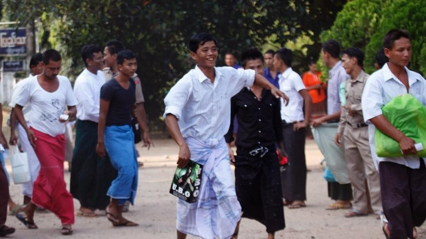 THIS CORRECTS SECOND SENTENCE - Myanmar prisoners walks after getting off a truck as they were released from Insein prison Tuesday, Oct. 7, 2014, in Yangon, Myanmar.  The Myanmar government pardoned 3,073 prisoners on Tuesday, but advocacy groups said no political prisoners were included despite a pledge by President Thein Sein to free all such detainees by the end of this year. (AP Photo/Khin Maung Win)