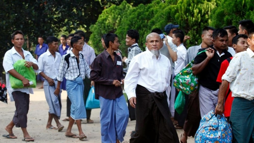 THIS CORRECTS SECOND SENTENCE- Myanmar prisoners walk to the entrance as they were released from Insein prison Tuesday, Oct. 7, 2014, in Yangon, Myanmar. The Myanmar government pardoned 3,073 prisoners on Tuesday, but advocacy groups said no political prisoners were included despite a pledge by President Thein Sein to free all such detainees by the end of this year. (AP Photo/Khin Maung Win)