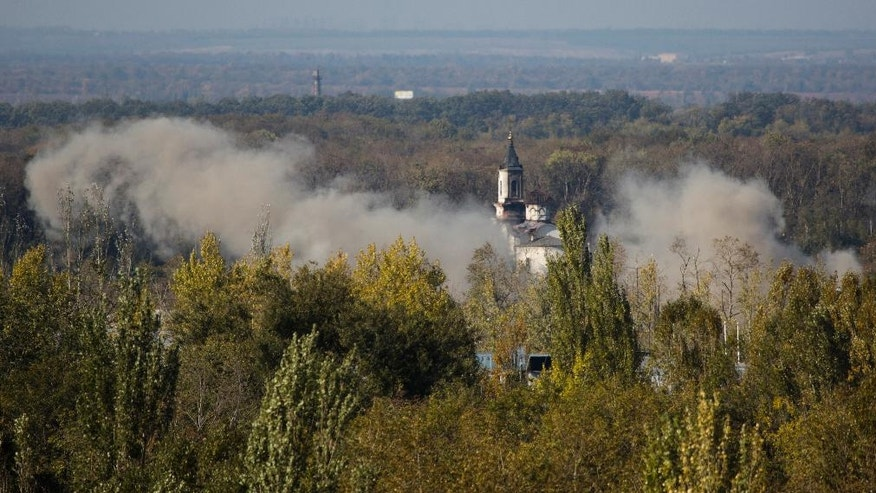 Smoke rises over the Svyato-Iversky Women's Monastery during artillery battle near to the airport in the town of Donetsk, eastern Ukraine Tuesday, Oct. 7, 2014.  Despite a cease-fire declared a month ago between the Ukrainian forces and pro-Russian rebels, the biggest city in eastern Ukraine remains embroiled in fighting .  (AP Photo/Dmitry Lovetsky)