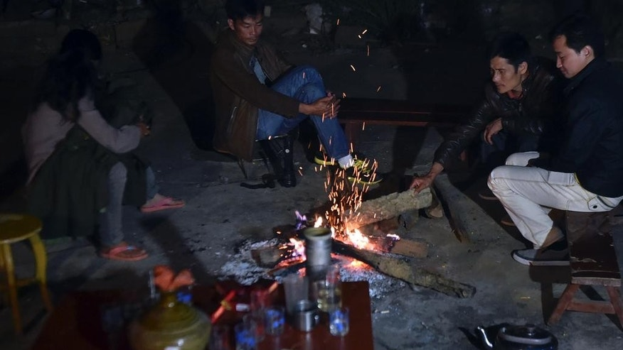 In this photo released by China's Xinhua News Agency, villagers take refuge in the open air at Mangla Village of Yongping Township at Jinggu County of Pu'er City, southwest China's Yunnan Province Wednesday, Oct. 8, 2014. A strong, shallow earthquake shook southwestern China overnight, killing at least one people, damaging buildings and prompting thousands to camp outside as aftershocks continued to strike the area, officials said Wednesday. (AP Photo/Xinhua, Chen Haining) NO SALES
