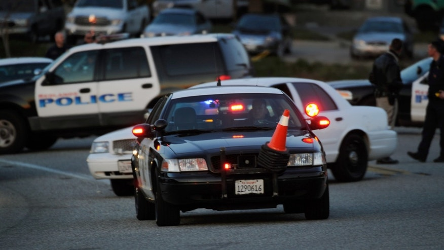 YUCAIPA, CA - FEBRUARY 12:  Redlands police officers secure at a blockade during a manhunt for the former Los Angeles Police Department officer Christopher Dorner who is suspected of triple murder on February 12, 2013 in Yucaipa, California. Dorner barricaded himself in a cabin near Big Bear, California and is in a standoff with authorities after shooting two police officers, killing one and wounding the other. Dorner, a former Los Angeles Police Department officer and Navy Reserve veteran, is wanted in connection with the deaths of an Irvine couple and a Riverside police officer.  (Photo by Kevork Djansezian/Getty Images)