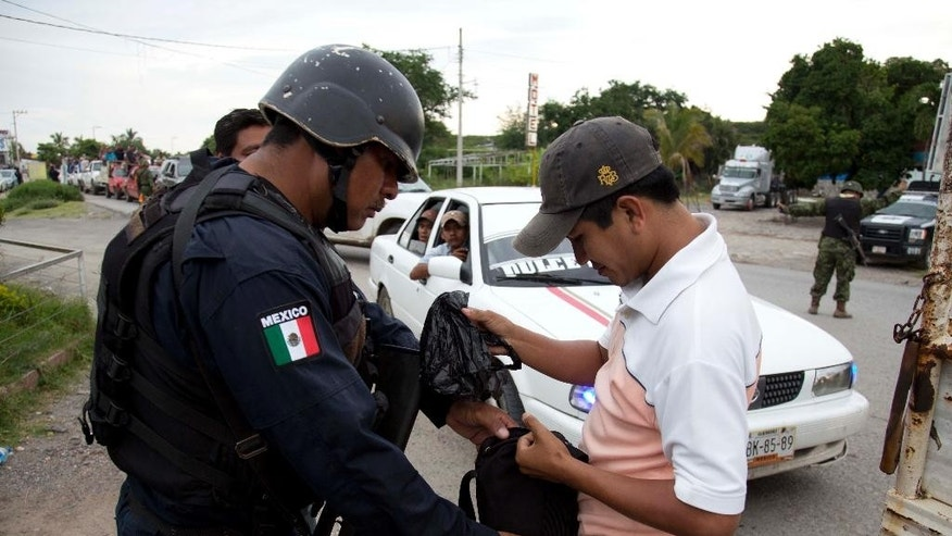 A State Police officer inspects the belongings a Community Police member in search of weapons as they arrive to help in the search for the missing students in Iguala, Mexico, Tuesday, Oct. 7, 2014. The students went missing after a Sept. 26 confrontation with local police that left six students and bystanders dead. Federal agents have been sent to the area after the discovery of a mass grave and charges that local police may have conspired with a criminal gang to kill and disappear the students. (AP Photo/Eduardo Verdugo)