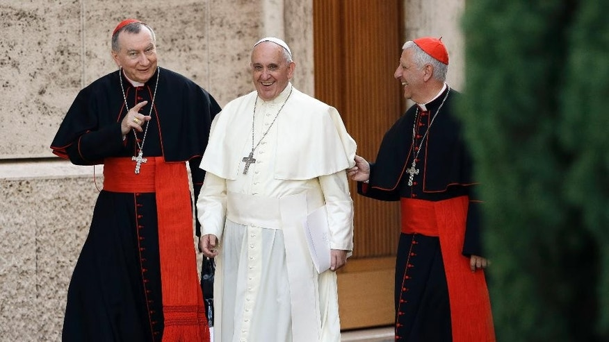 Pope Francis smiles as he walks alongside Vatican Secretary of State Pietro Parolin, left, and Cardinal Giuseppe Versaldi, prior to start an afternoon session of a two-week synod on family issues at the Vatican, Wednesday, Oct. 8, 2014. (AP Photo/Gregorio Borgia)