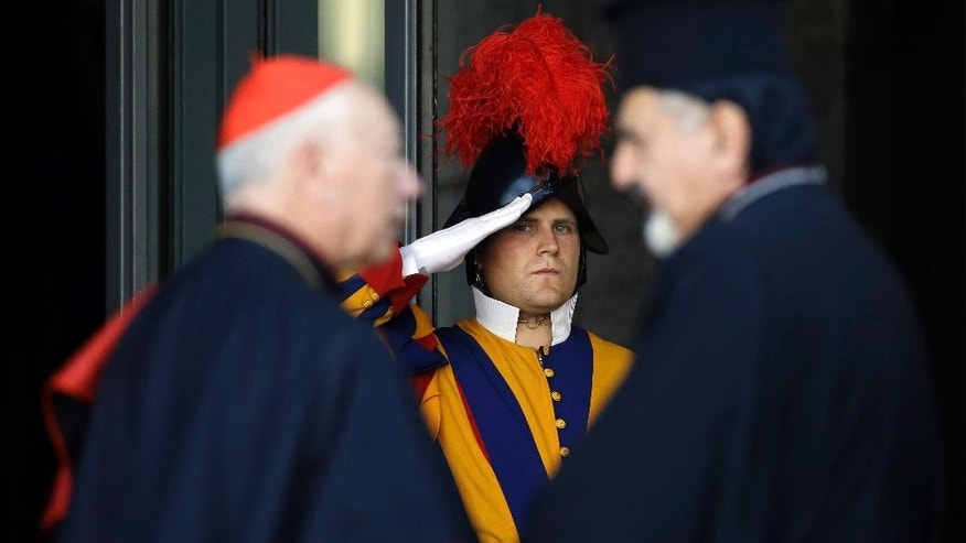 A Swiss guard salutes as prelates arrive for an afternoon session of a two-week synod on family issues at the Vatican, Wednesday, Oct. 8, 2014. (AP Photo/Gregorio Borgia)