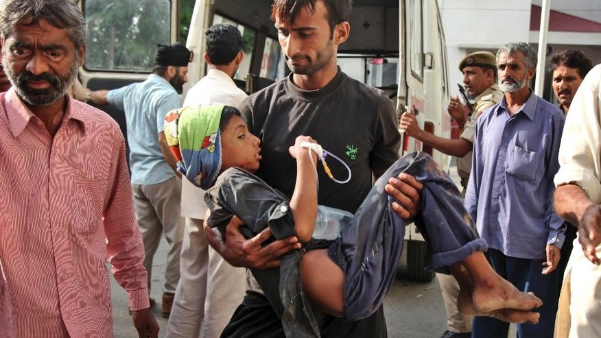 An Indian man carries a boy, injured reportedly in firing and shelling from Pakistan side at Jora farm in Ranbir Singh Pura of the India-Pakistan border, for treatment to the government medical college hospital, in Jammu, India, Wednesday, Oct. 8, 2014. Indian and Pakistani troops fired bullets and mortar shells across the border between Kashmir and Pakistan for a second day Tuesday, with both accusing the other of provoking the violence. (AP Photo/Channi Anand)