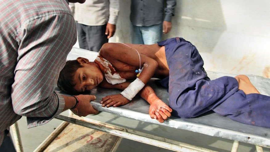 An injured Indian boy is carried on a stretcher for treatment to the government medical college hospital, in Jammu, India, following firing from the Pakistani side of the border in Samba, Wednesday, Oct. 8, 2014. Indian and Pakistani troops fired bullets and mortar shells across the border between Kashmir and Pakistan for a second day Tuesday, with both accusing the other of provoking the violence. (AP Photo/Channi Anand)