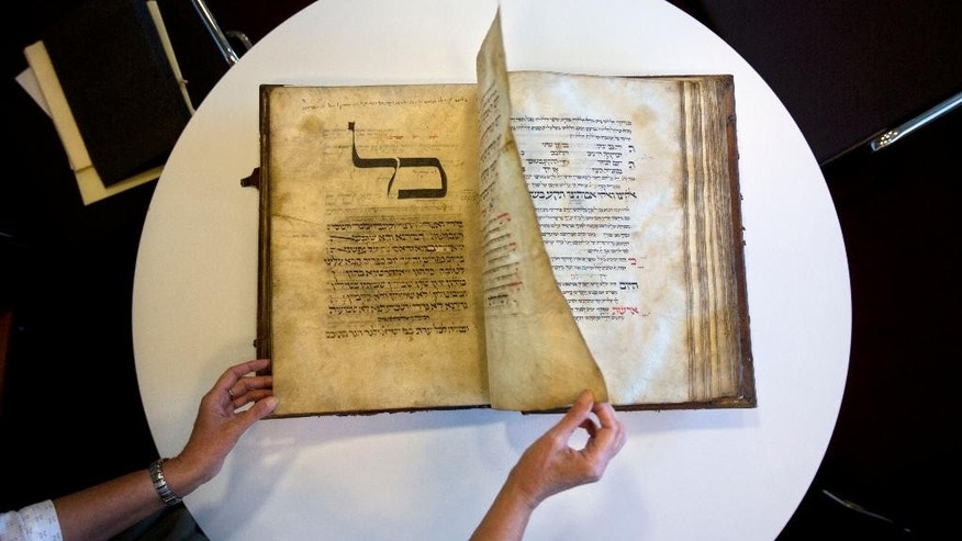 In this photo taken Sunday, Oct. 5, 2014, a library official shows a 13th-century German prayer book containing the earliest evidence of the Yiddish language, at Israel's National Library in Jerusalem. This week, Israel's National Library gave The Associated Press a rare peek at a selection of rare historical manuscripts in its collection. (AP Photo/Sebastian Scheiner)