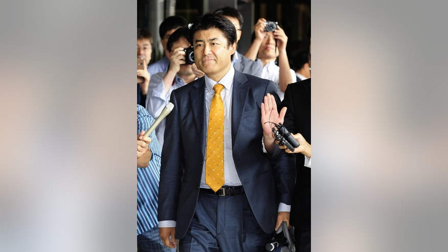 In this photo taken August 2014, then-Sankei Shimbun Chief of Bureau Tatsuya Kato, surrounded by reporters arrives at Seoul District Court in Seoul, South Korea. South Korean and Japanese media say Kato has been indicted on charges he defamed South Korea's president in an online story. The allegations against the Japanese newspaper's reporter have raised questions about South Korean press freedom. The indictment by Seoul prosecutors on Wednesday, Oct. 8, 2014 which was confirmed by the newspaper, comes amid rising animosity between the countries. (AP Photo/Kyodo News) JAPAN OUT, CREDIT MANDATORY