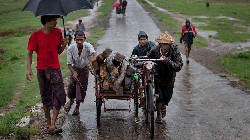 In this June 26, 2014 photo, Rohingya men push a trishaw loaded with woods in Thet Kabyin village, north of Sittwe, Rakhine State, Myanmar. Almost all Rohingya were excluded from a U.N.-funded nationwide census earlier this year, the first in three decades, because they did not want to register as Bengalis. (AP Photo/Gemunu Amarasinghe)