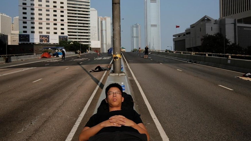 A pro-democracy supporter sleeps on the streets in the occupied areas surrounding the government complex in Hong Kong Wednesday, Oct. 8, 2014. Crowds of protesters who filled Hong Kong's streets with demands for more democracy thinned dramatically Tuesday after student leaders and the government agreed to hold talks in the increasingly frustrated city. (AP Photo/Vincent Yu)