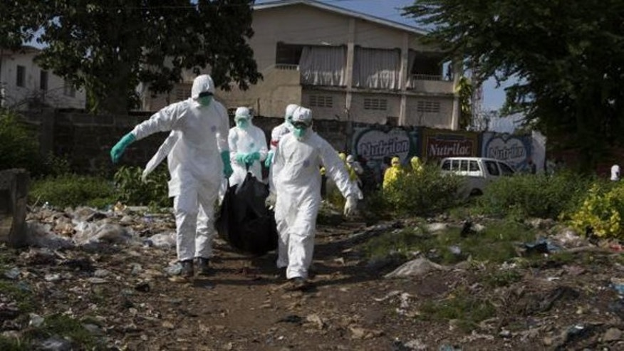 September 28, 2014: A burial team wearing protective clothing remove a body of a person suspected of having died of the Ebola virus in Freetown, Sierra Leone (REUTERS/Christopher Black/WHO/Handout via Reuters)