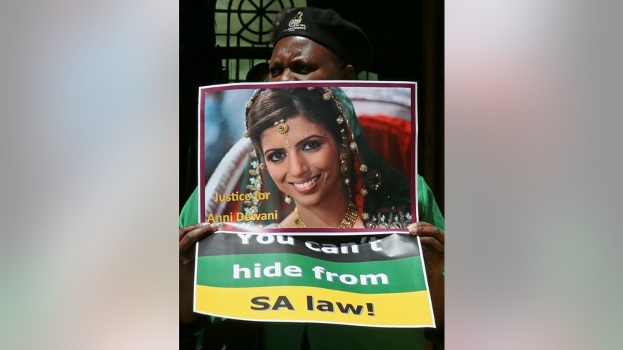 "A protester holds a placard with a portrait of the late Anni Dewani that reads ""You cannot hide from SA (South Africa) law"" outside the Cape Town, South Africa,  high court, Wednesday, Oct. 8, 2014. as the trial of British businessman and murder accused Shrien Dewani continued for a second day. Dewani is charged with orchestrating the murder of his wife, Anni, while the newly-married couple were on honeymoon in South Africa in 2010. (AP Photo/Nardus Engelbrecht)"