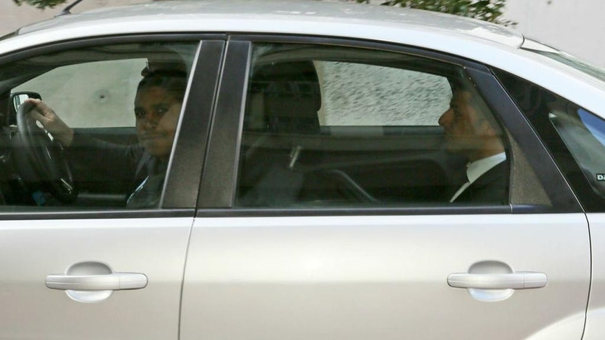 British businessman and accused murder suspect Shrien Dewani, right, is driven away in a car from the High Court in Cape Town, South Africa, Wednesday, Oct. 8, 2014, as his trail continues for a second day.  Dewani is charged with orchestrating the murder of his wife, Anni, while the newly-married couple were on honeymoon in South Africa in 2010. (AP Photo/Nardus Engelbrecht)