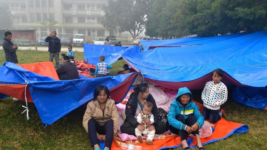 Residents gather outdoor in the aftermath of an earthquake in the town of Yongping of Jinggu county in southwest China's Yunnan province Wednesday Oct. 8, 2014.  A strong, shallow earthquake with a magnitude of at least 6.0 shook southwestern China overnight, killing at least one person, damaging buildings and prompting thousands to camp outside as aftershocks continued to strike the area, officials said Wednesday. (AP Photo) CHINA OUT