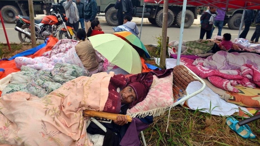 Residents rest outdoor in the aftermath of an earthquake in the town of Yongping of Jinggu county in southwest China's Yunnan province Wednesday Oct. 8, 2014.  A strong, shallow earthquake with a magnitude of at least 6.0 shook southwestern China overnight, killing at least one person, damaging buildings and prompting thousands to camp outside as aftershocks continued to strike the area, officials said Wednesday. (AP Photo) CHINA OUT