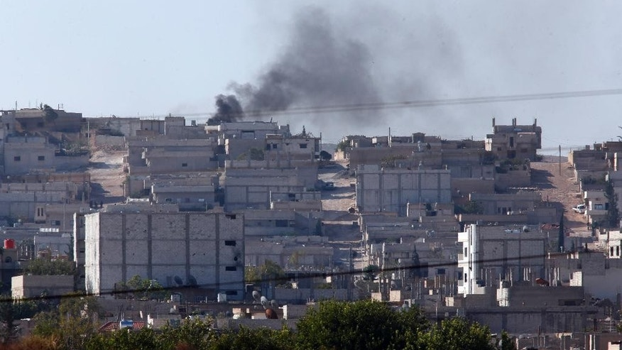 Smoke rises after a strike in Kobani, Syria as fighting intensifies between Syrian Kurds and the militants of Islamic State group, as seen from Mursitpinar on the outskirts of Suruc, at the Turkey-Syria border,  Wednesday, Oct. 8, 2014. Kobani has been under the onslaught of the Islamic State group since mid-September when the militants' launched their offensive in the area, capturing several Kurdish villages around the town and bringing Syria's civil war yet again to Turkey's doorstep.  (AP Photo/Lefteris Pitarakis)