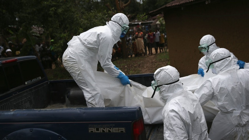 MONROVIA, LIBERIA - OCTOBER 08:  A burial team from the Liberian Red Cross carries the body of an Ebola victim from his home on October 8, 2014 near Monrovia, Liberia. The Ebola epidemic has killed more than 3,400 people in West Africa, according to the World Health Organization. (Photo by John Moore/Getty Images)