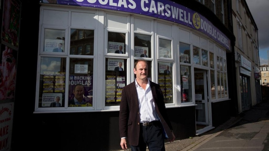 In this picture taken on Tuesday, Oct. 7, 2014, Douglas Carswell, the UK Independence Party (UKIP) candidate for the Clacton by-election, poses for photographs outside his campaign offices in Clacton-on-Sea, England. The U.K. Independence Party is finding a warm welcome in this seaside town for its promise to curb immigration and leave the European Union. But the invasion washing up here isn't from across the water _ it's an army of UKIP supporters from around the country, flocking to Clacton-on-Sea to help the party make an electoral breakthrough that could change the face of British politics. (AP Photo/Matt Dunham)