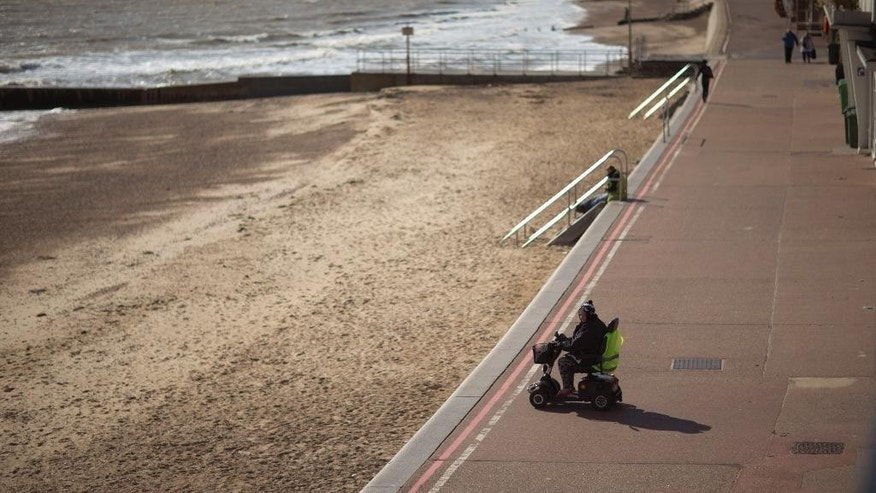 In this picture taken on Tuesday, Oct. 7, 2014, a woman sits in a mobility scooter by Clacton Beach in Clacton-on-Sea, England. The U.K. Independence Party is finding a warm welcome in this seaside town for its promise to curb immigration and leave the European Union. But the invasion washing up here isn't from across the water _ it's an army of UKIP supporters from around the country, flocking to Clacton-on-Sea to help the party make an electoral breakthrough that could change the face of British politics. (AP Photo/Matt Dunham)