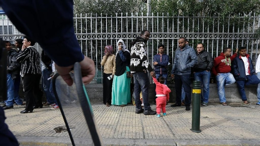 Immigrants from various countries queue outside Greece's Central Asylum Service in Athens on Wednesday, Oct. 8, 2014. The United Nations refugee agency is calling on the European Union to overhaul its policy toward Syrian refugees, warning the number of fatal accidents at sea could rise further as winter approaches. Greek authorities says they expect a three-fold increase in the number of would-be immigrants and asylum seekers apprehended this year, compared with 2013, with most now coming from Syria. (AP Photo/Thanassis Stavrakis)