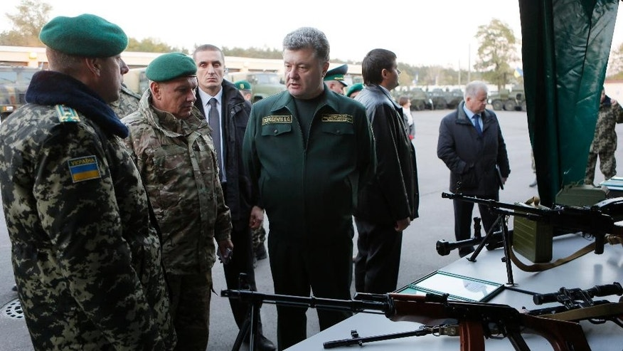 Ukrainian President Petro Poroshenko, center, inspects military weapons during his visit in a State Border Guard Service  in Kiev, Ukraine, Tuesday, Oct. 7, 2014. (AP Photo/Sergei Chuzavkov)