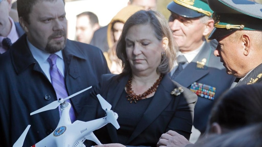 Assistant Secretary for European and Eurasian Affairs Victoria Nuland, center, examines mini helicopter  during her visit in a State Border Guard Service in Kiev, Ukraine, Wednesday, Oct. 8, 2014. Speaking in Kiev this week, Nuland condemned continued violations of a Sept. 5 cease-fire deal between Ukrainian government troops and separatists in the east and called for the withdrawal of foreign troops and equipment from the area affected by conflict. (AP Photo/Efrem Lukatsky)
