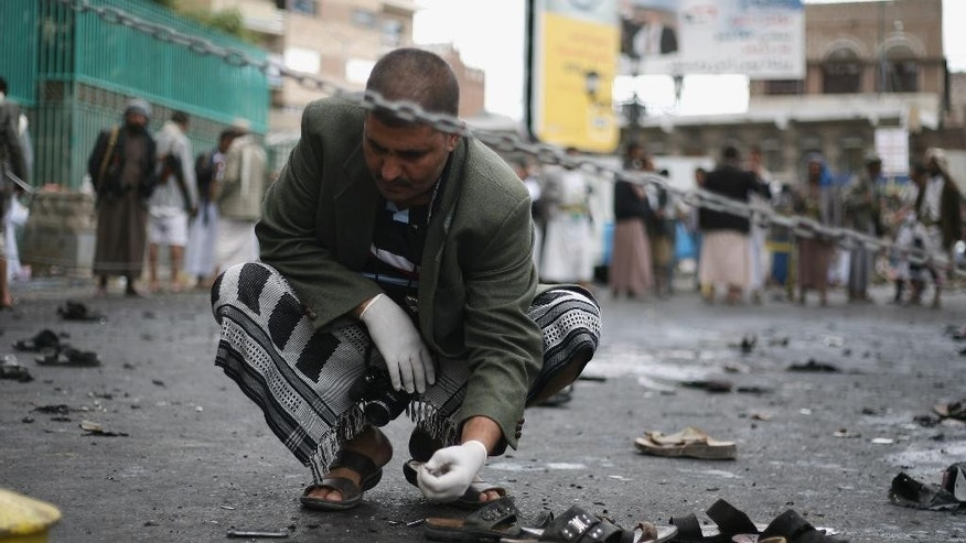 A Yemeni security official inspects the site of a suicide bombing in Sanaa, Yemen, Thursday, Oct. 9, 2014. A suicide bomber struck at the center of the Yemeni capital of Sanaa on Thursday, setting off his explosives at a gathering of supporters of the rebel Shiite Houthis who recently overran the city, security officials said. (AP Photo)